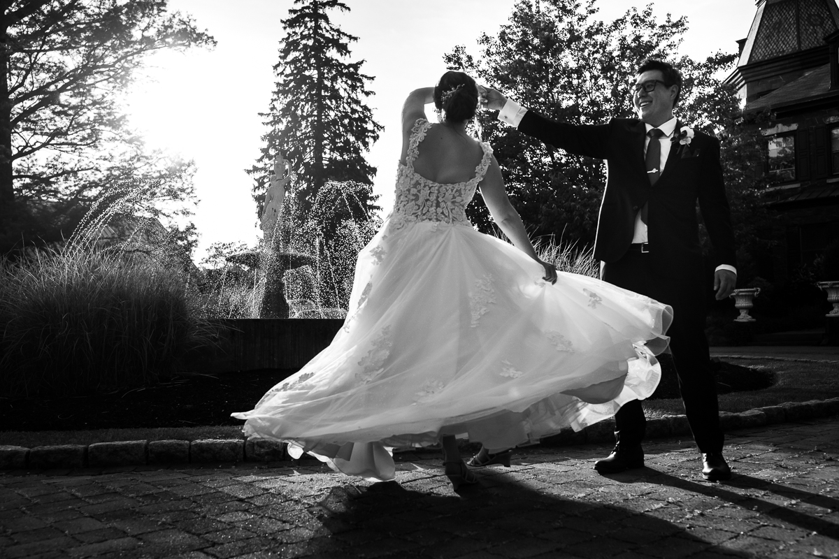 bride is twirled during her mount hope estate wedding day in a black and white image showing her dancing dress