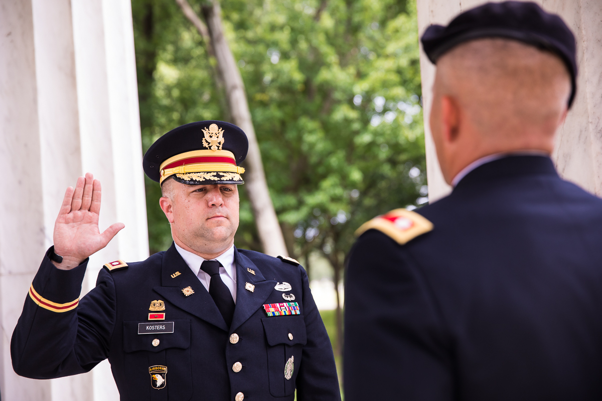 new army colonel being sworn into new position after being promoted wearing uniform with one hand up outside on DC war memorial