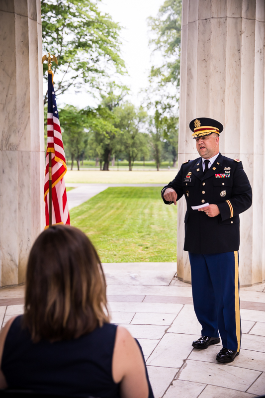 newly promoted colonel giving speech after promotion at DC war memorial best DC family photographer military promotion ceremony outside with American flag in background