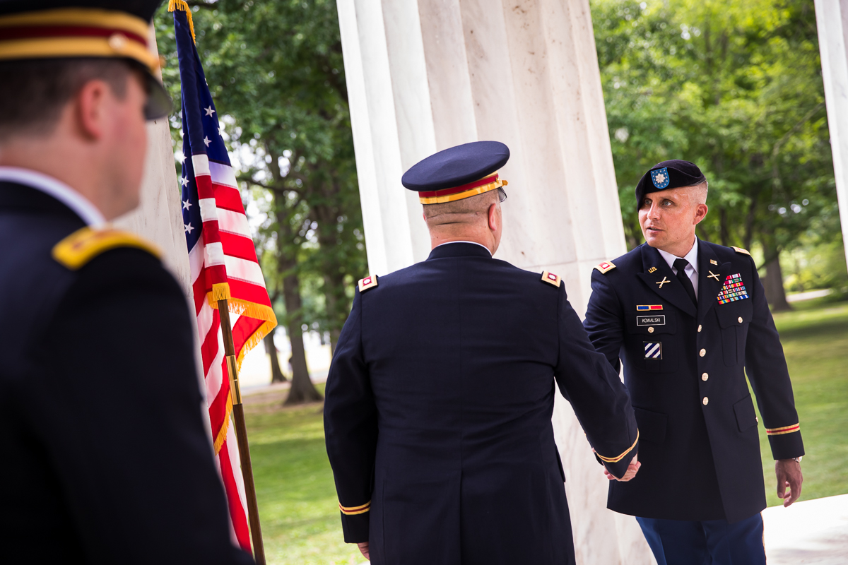 army officers shaking hands after military promotion to colonel with American flag in background on DC memorial best military promotion family photographer