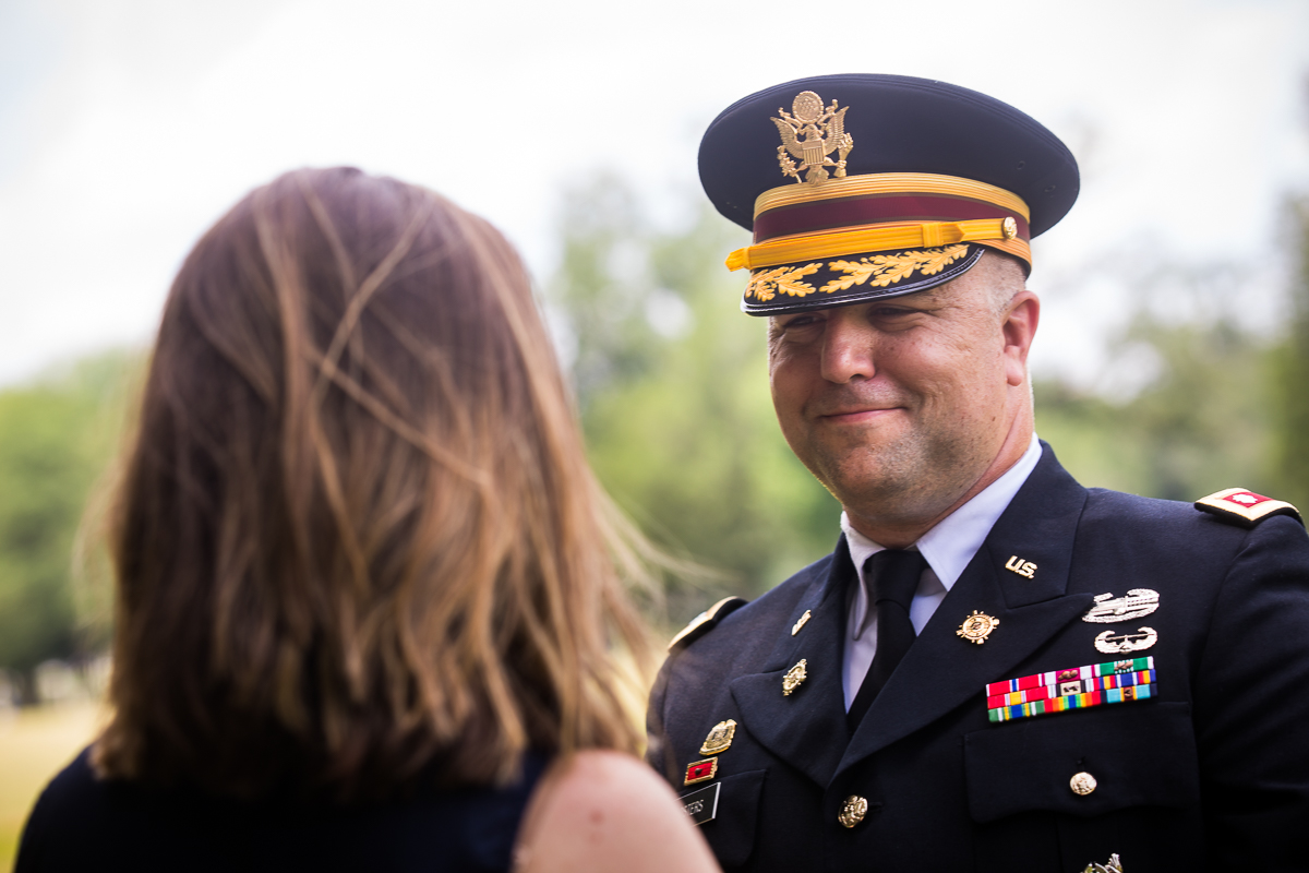 husband smiling at wife wearing army uniform after being promoted to colonel during military promotion ceremony