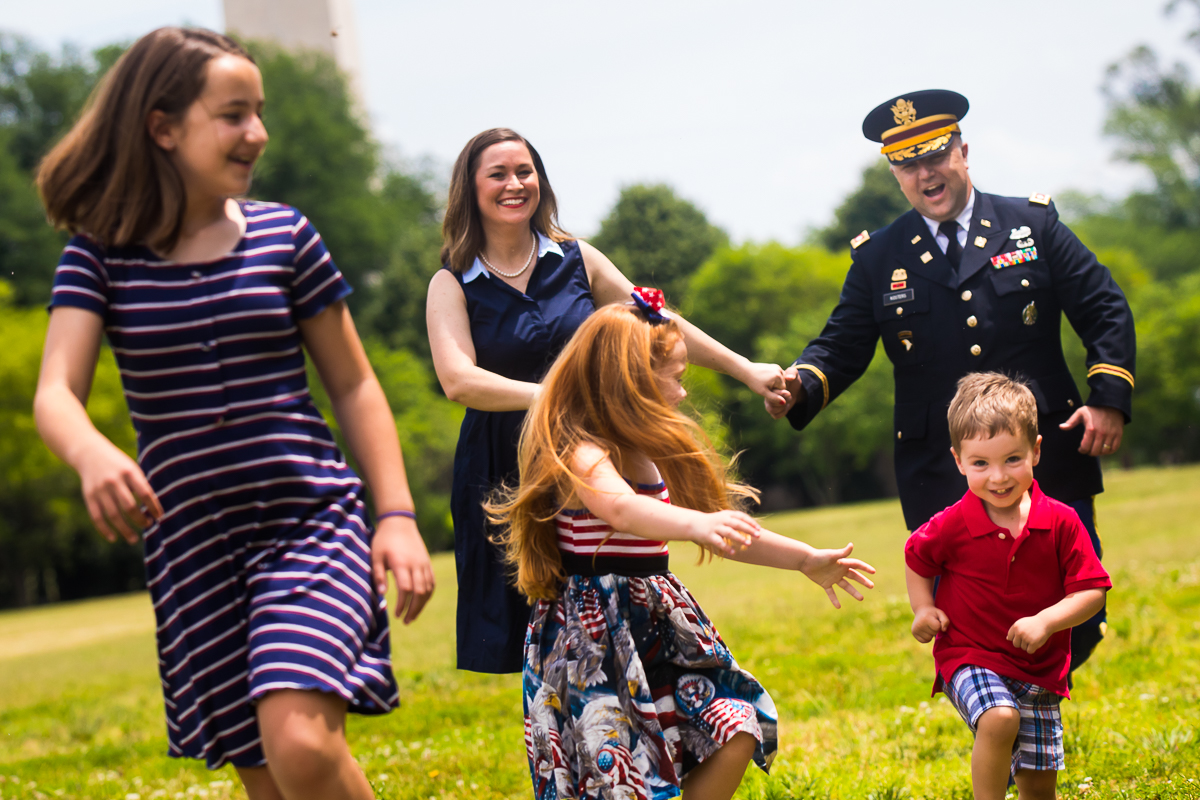 DC family running through park after military promotion ceremony smiling laughing with each other best candid photographer