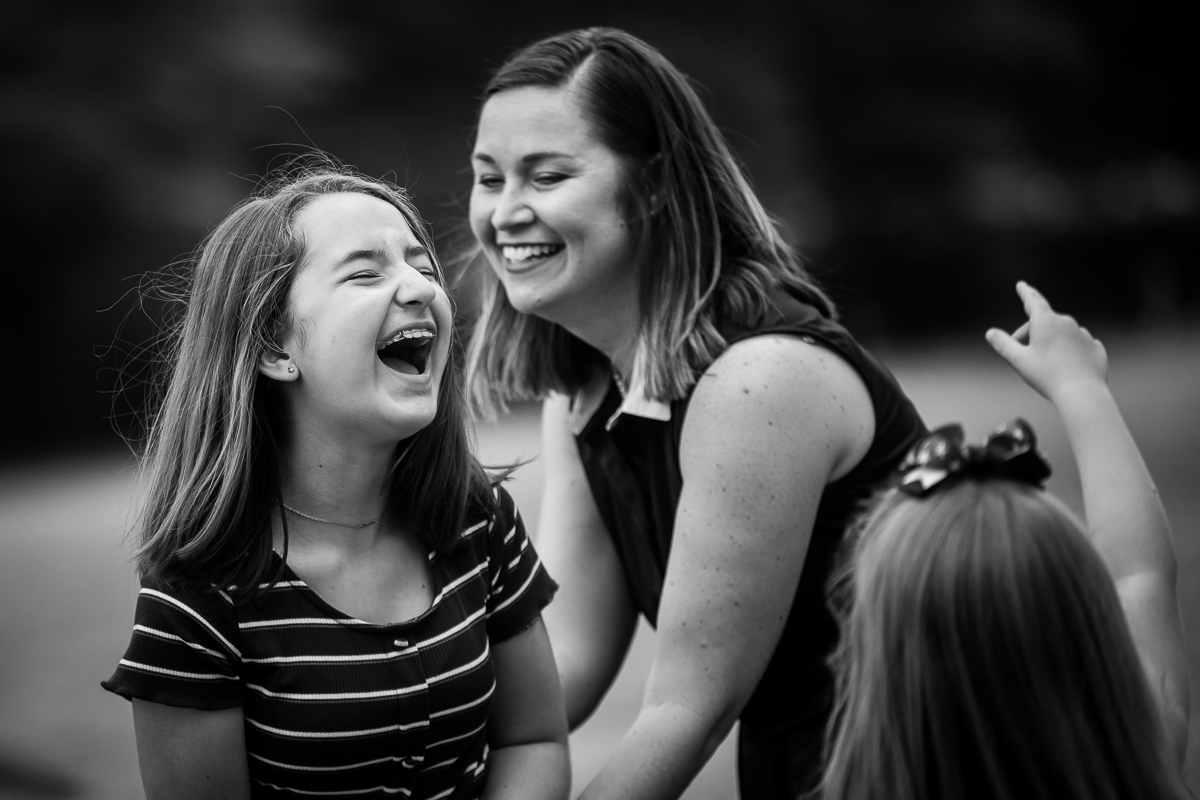 black and white photo of mom and siblings laughing with each other best DC family photographer