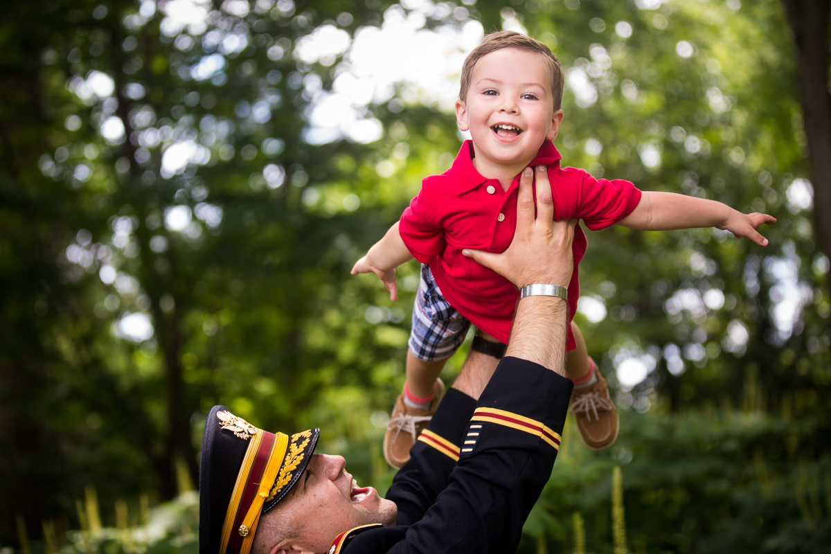 dad holding son in air while son smiles at camera after DC military promotion photographer candid natural best