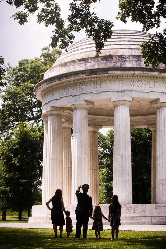 family silhouetted holding hands while facing DC war memorial best DC family photographer military promotion ceremony