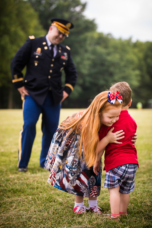 girl wearing American flag eagle print dress hugging brother while dad an army colonel smiles from a distance outside dc touching candid moment best award winning photographer