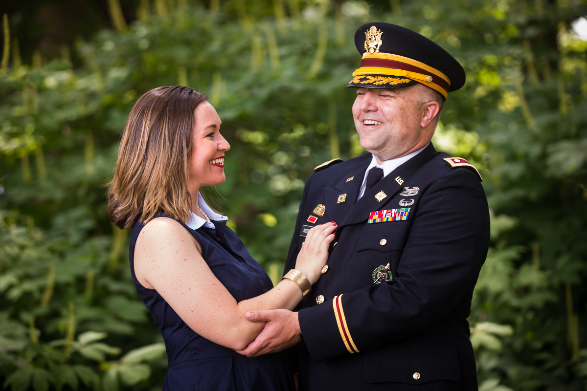 husband who was just promoted to army colonel holds and laughs with wife outside military DC family photographer
