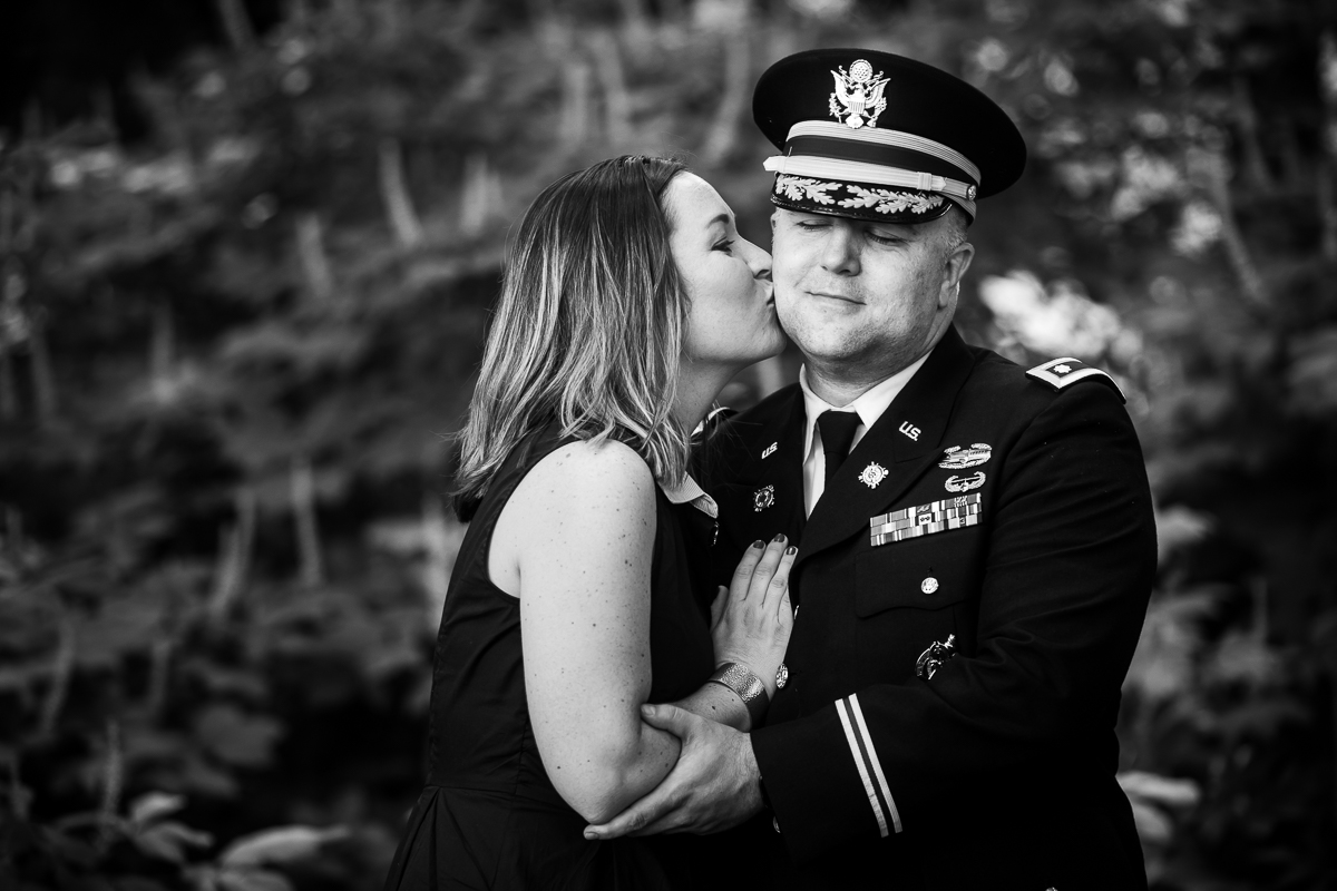 black and white photo of wife kissing husband in army uniform dc family photographer traditional portrait best dc photographer