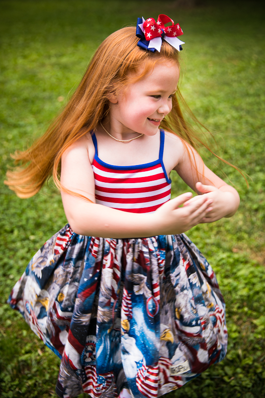 red headed girl spinning while wearing red white and blue eagle American flag printed dress with bow in hair outside DC