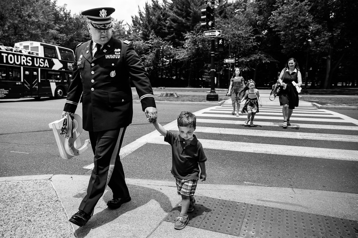 black and white candid photo of colonel in army holding son's hand while family follows behind walking on crosswalk