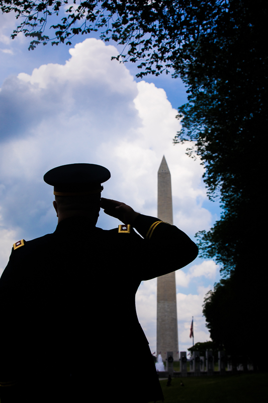 army colonel saluting to flag silhouetted against blue cloudy sky with pentagon and flag in background