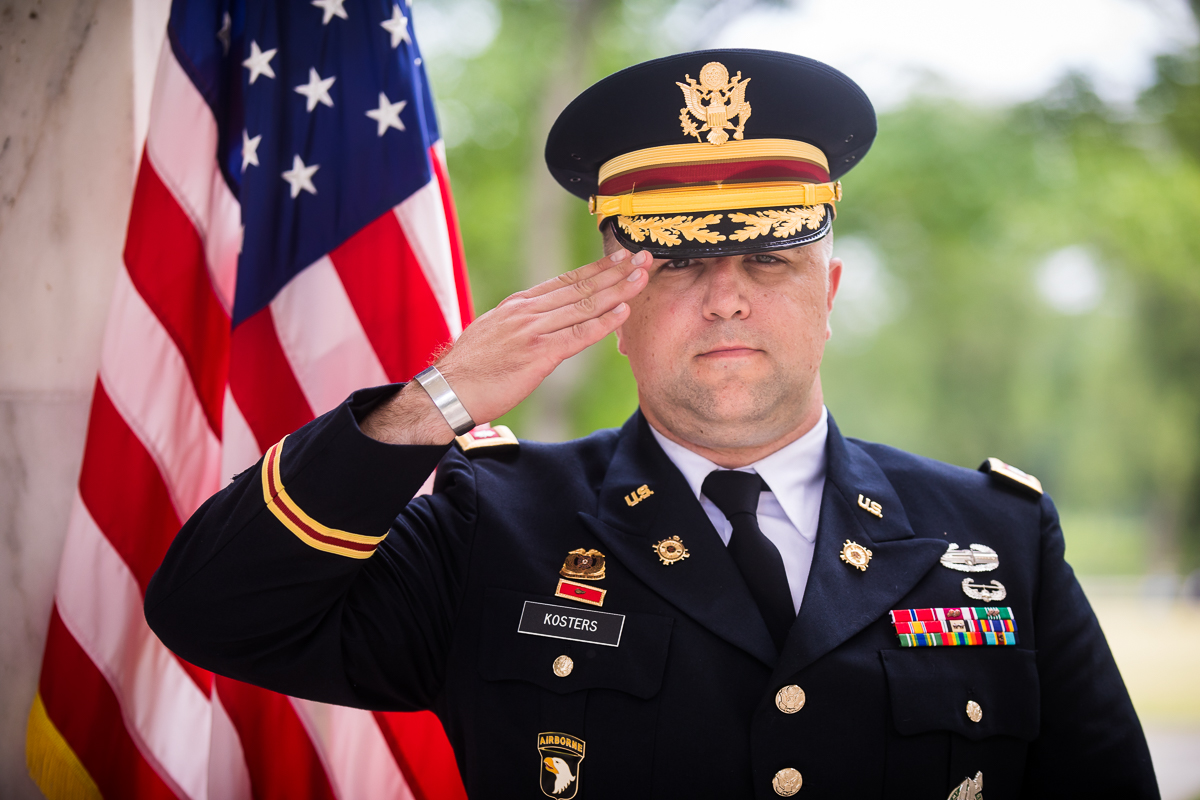 army colonel saluting while standing in front of American flag wearing uniform outside during promotion ceremony