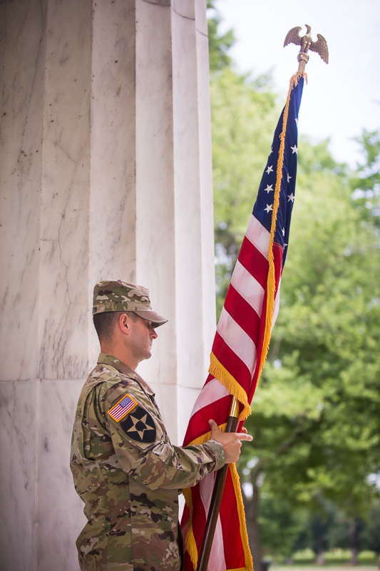 army man wearing camouflage uniform holding American flag during military promotion ceremony