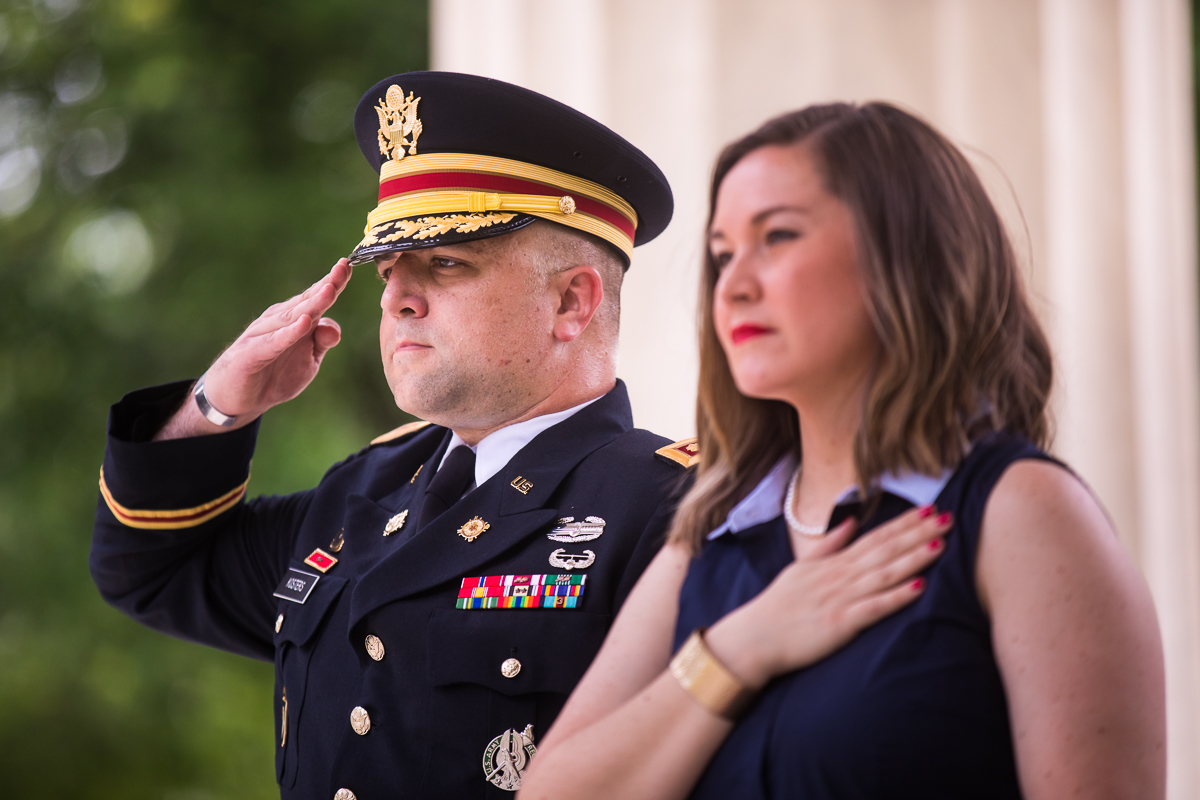 army colonel saluting while wife stands next to him with hand over heart during pledge of allegiance during DC military promotion ceremony