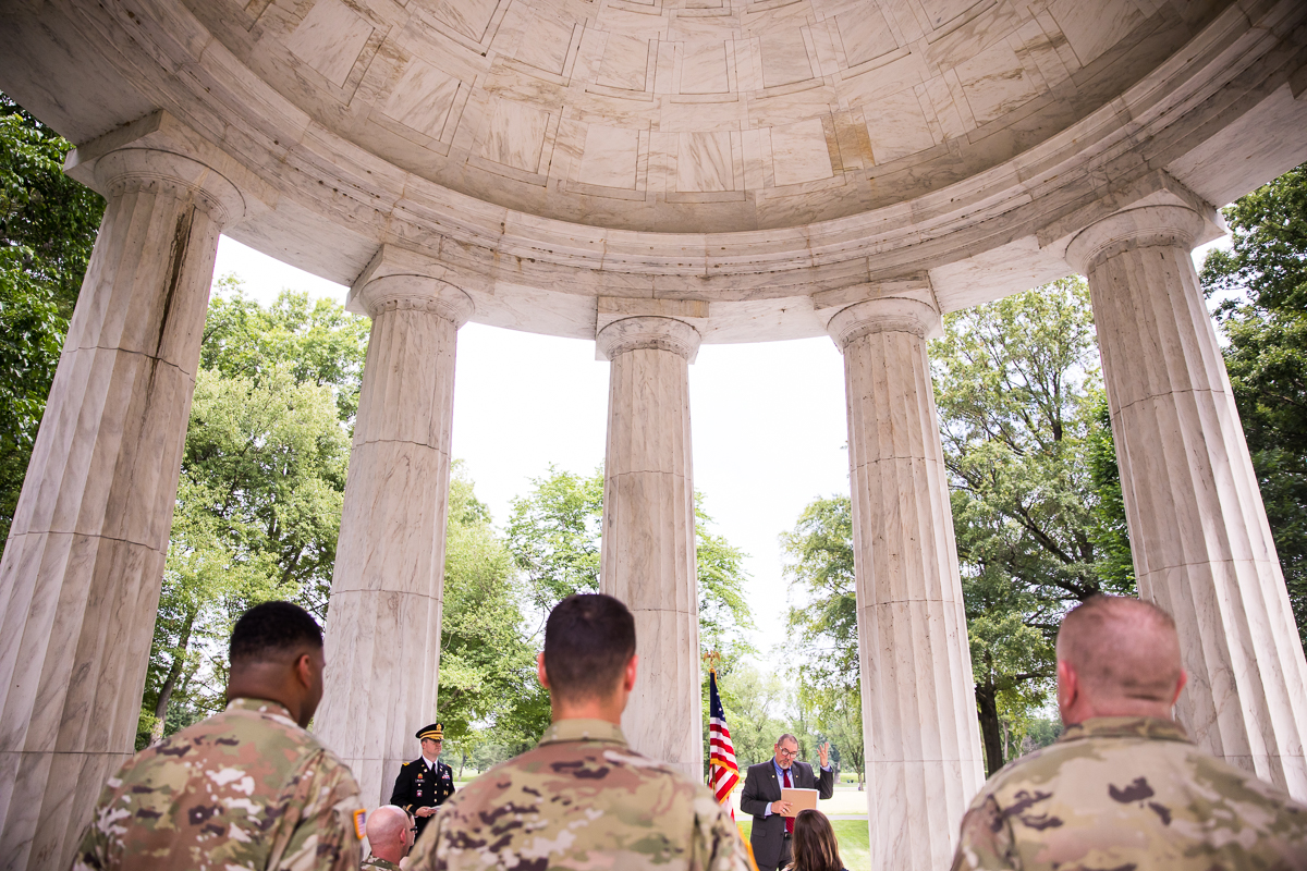 army men wearing camouflage uniforms standing watching military promotion ceremony DC family photographer unique perspective under war memorial