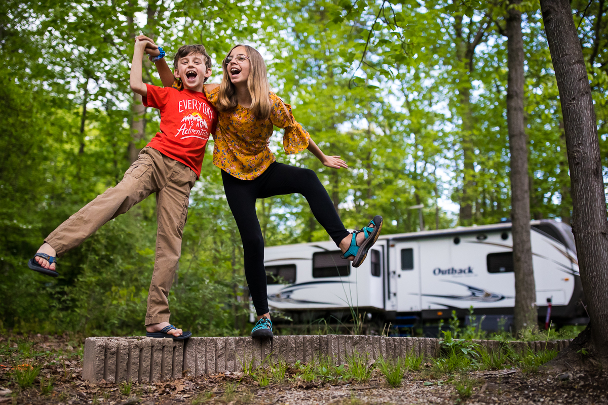 brother and sister walking along concrete blocks in front of rv at campsite rv family photographer