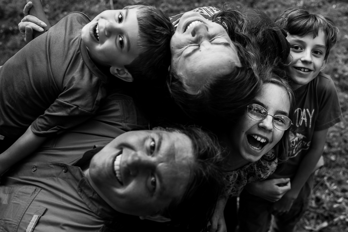 black and white photo of family of five smiling while laying on each other outside at rv campsite rv family photographer