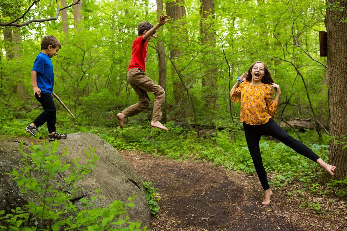 homeschooling family portrait photographers capture kids playing barefoot in the woods creative best natural authentic family lifestyle photographer