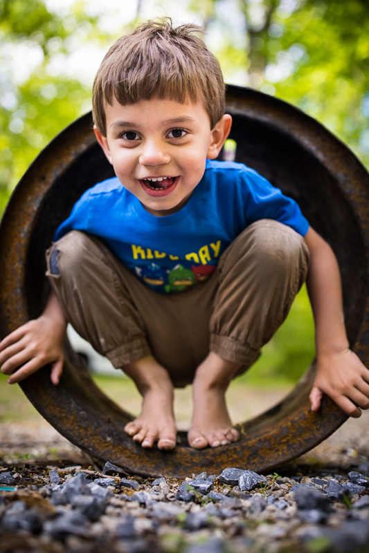 boy smiling at camera while standing barefoot inside pipe outside traditional portrait pa family photographer