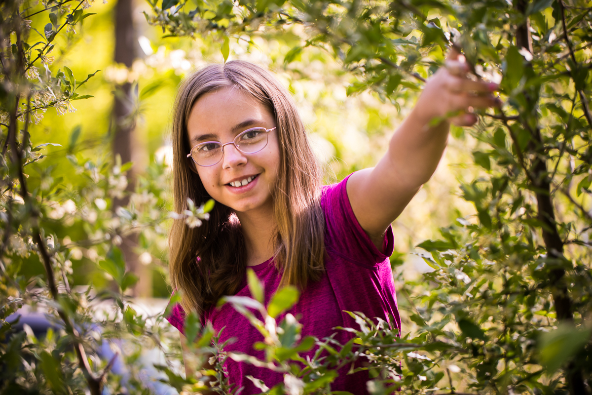 girl with glasses holding back branch surrounded by flowers and nature smiling at camera best pa family photographer