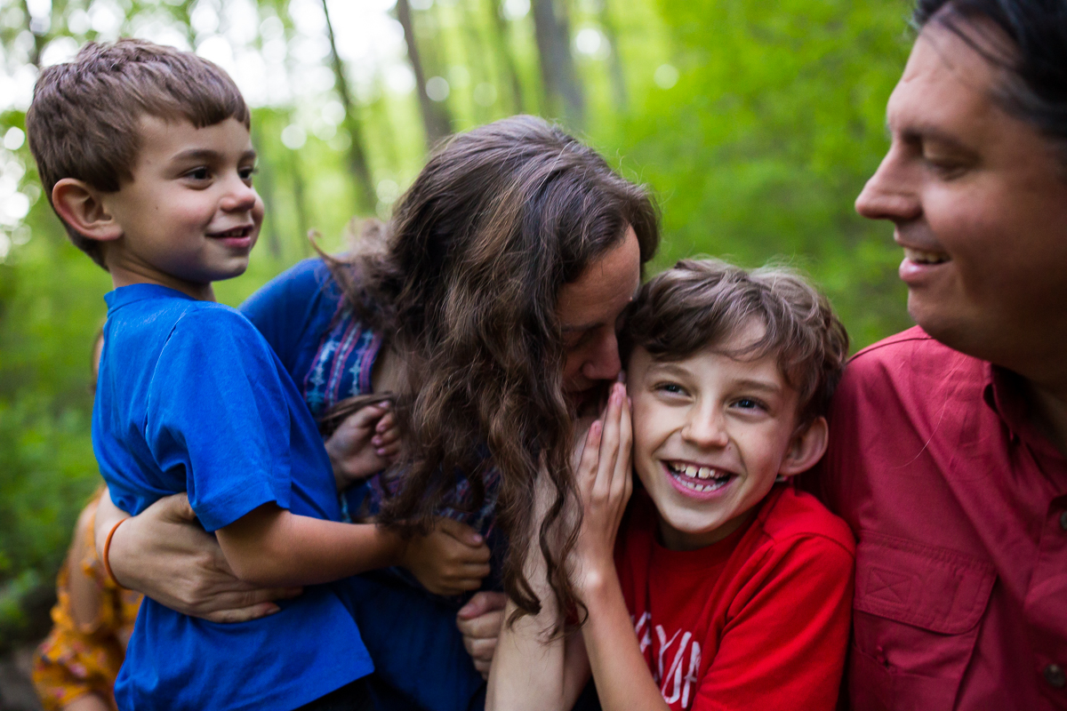 family lifestyle photographer creatively captures authentic family moments playing whisper down the alley outdoors at campsite