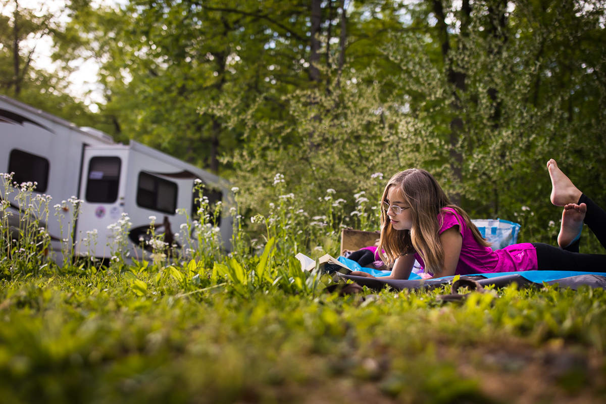 rv lifestyle photographer girl laying in grass on blanket reading book outdoors in front of rv parked at campsite