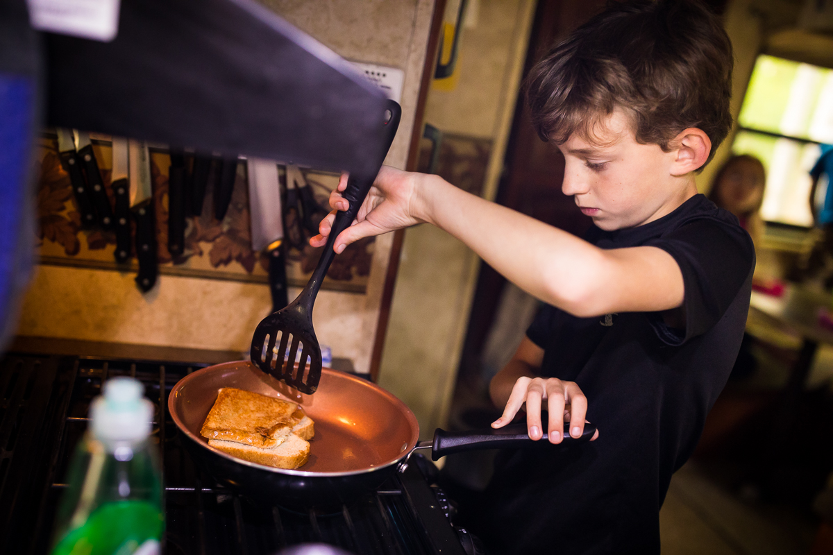 boy inside rv making grilled cheese sandwich on stove holding spatula