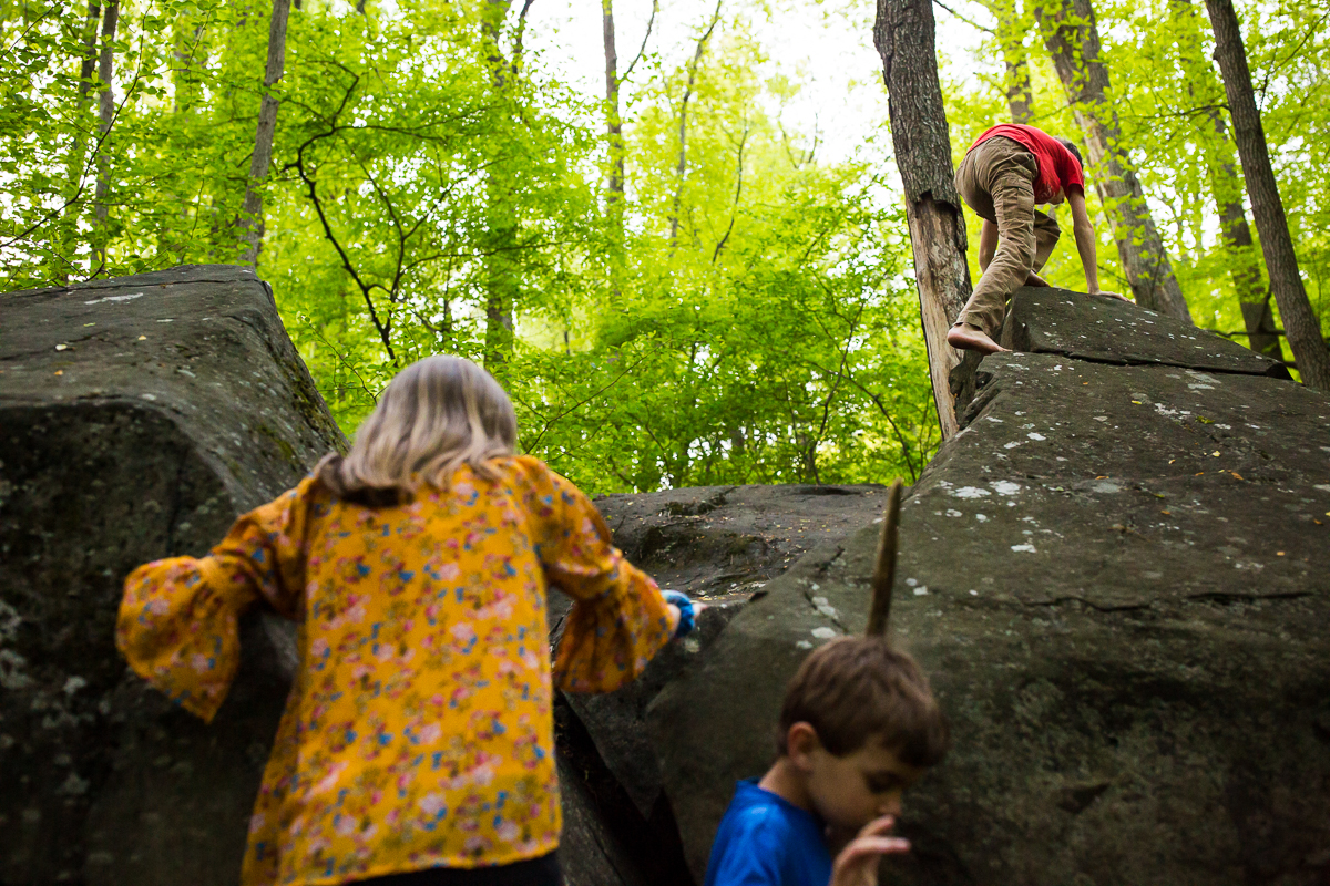 brothers and sister playing outdoors in nature climbing on rocks surrounded by trees best creative pa photographer
