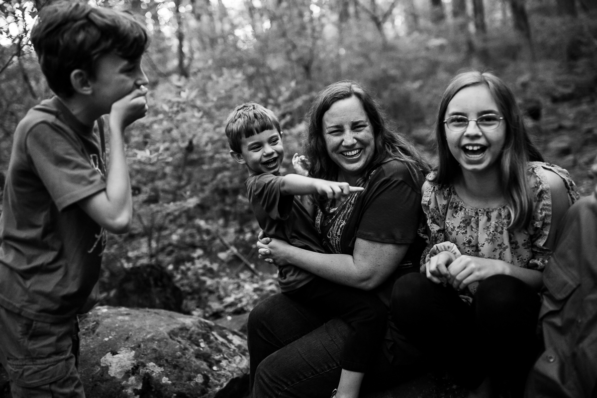 family lifestyle photographer captures emotional black and white photo of mom with children smiling and laughing outside