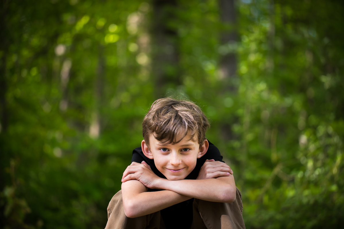 boy sitting with elbows across knees smiling at camera in center traditional portrait photographer pa