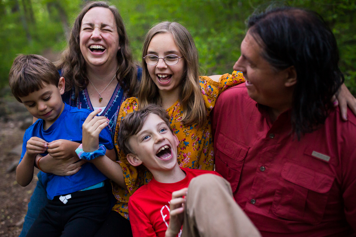 family of five smiling and laughing with each other outdoors in nature best candid natural artistic family photographer pennsylvania