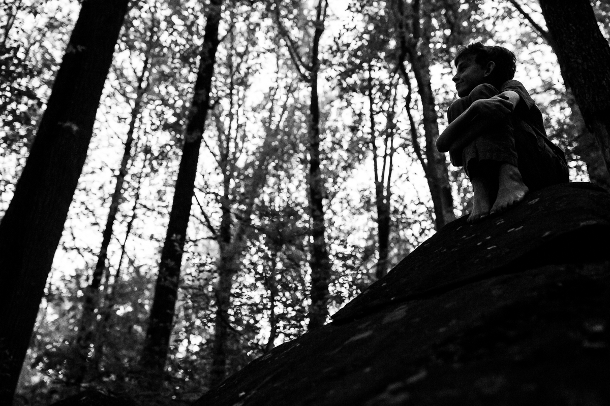 black and white photo of boy hugging knees to chest smiling looking off in the distance surrounded by tall trees