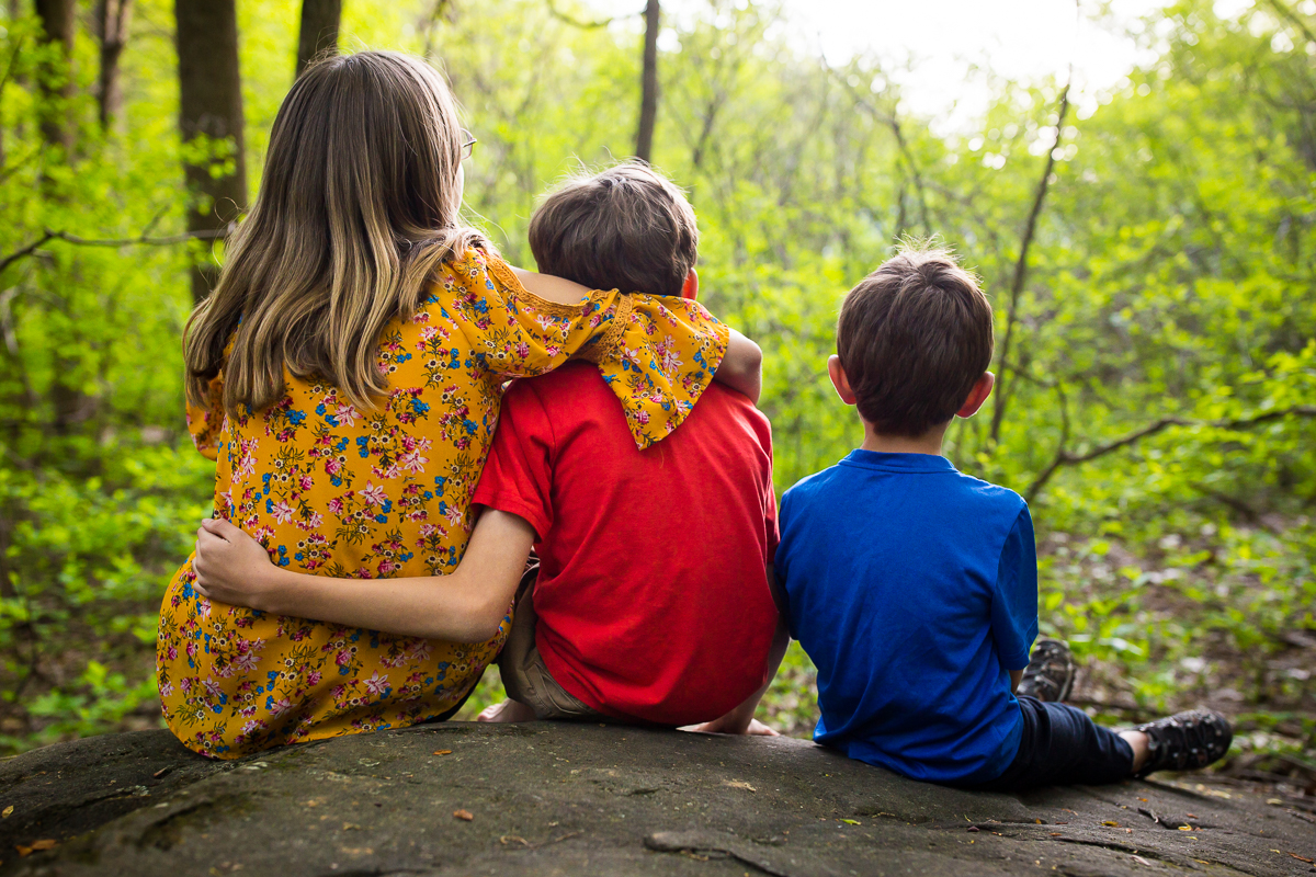 family lifestyle photographer captures brothers and sister sitting on rocks with arms around each other looking off into distance