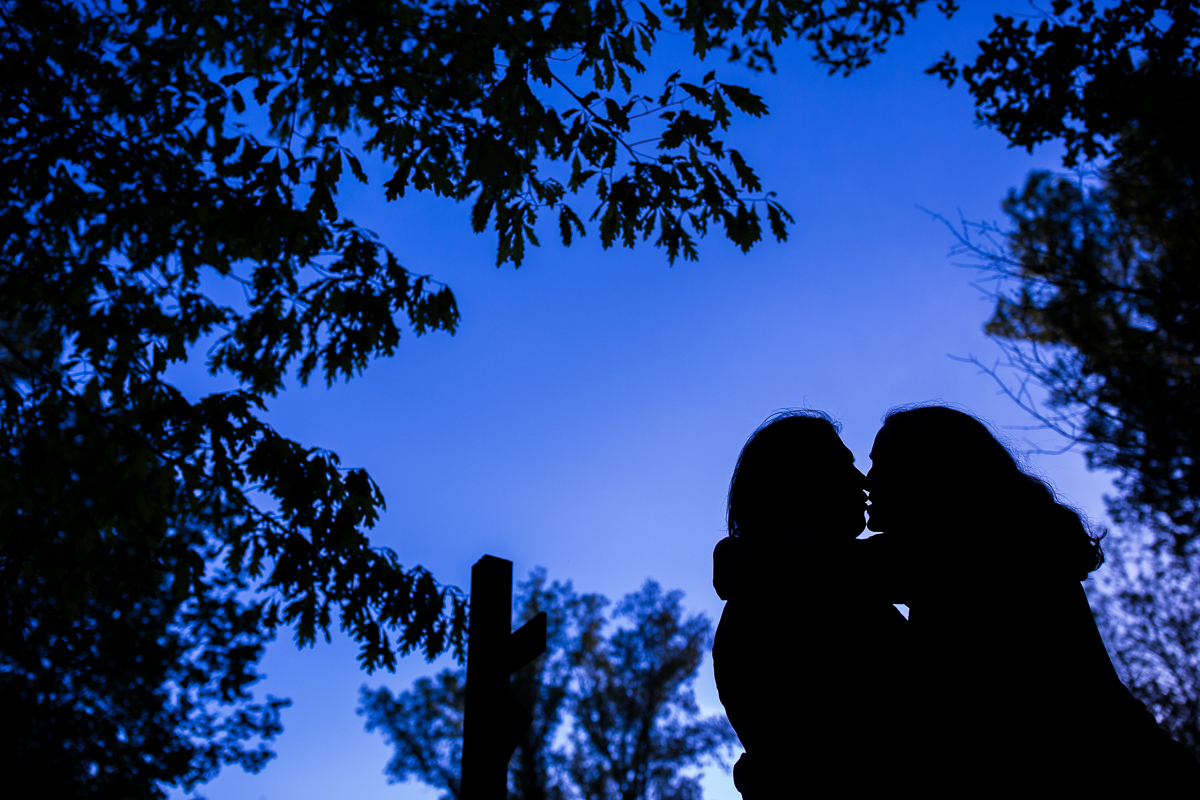 rv family photographer husband and wife with deep blue sky silhouetted against background embracing with foliage surrounding