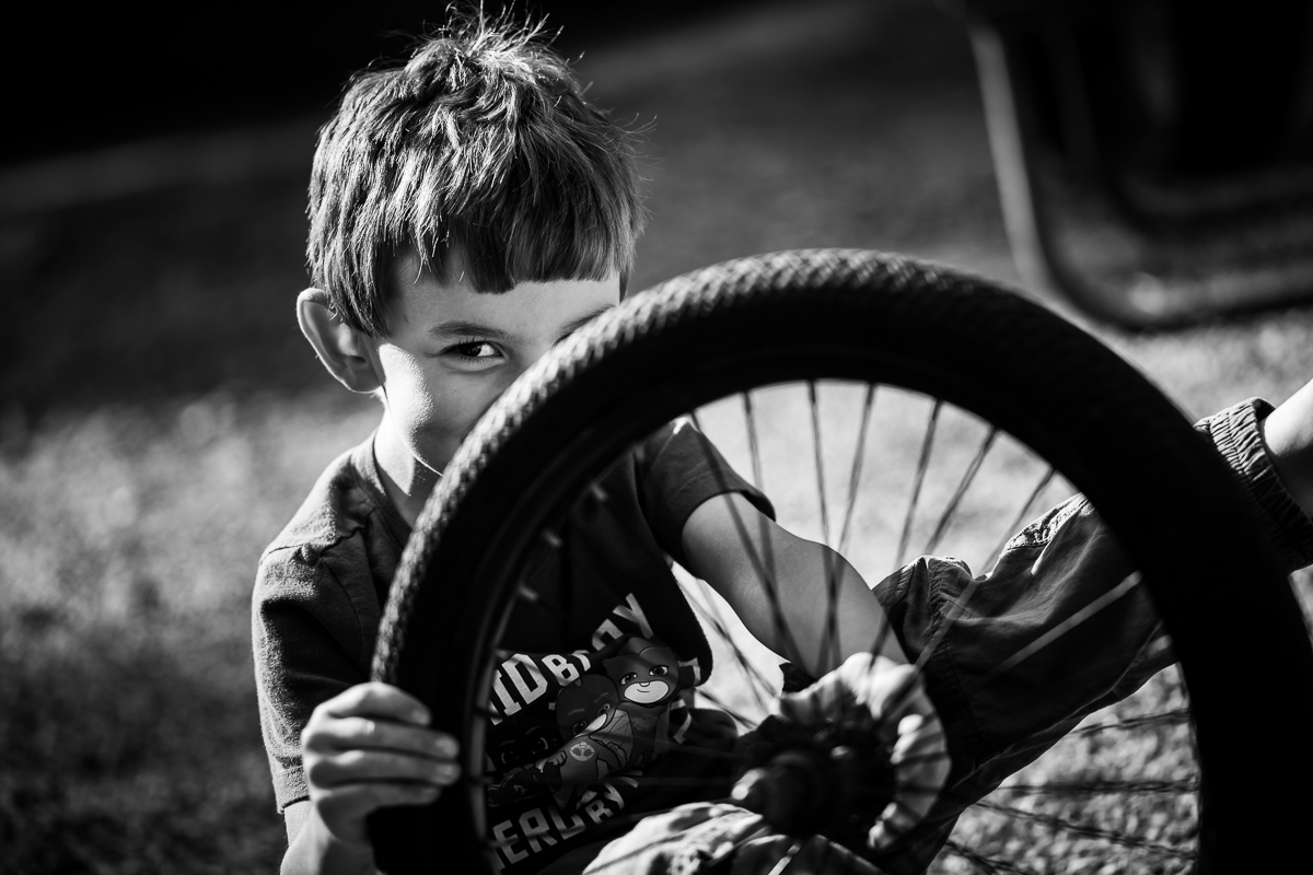 black and white photo of boy playing with bike tire smiling creative artistic angle portrait
