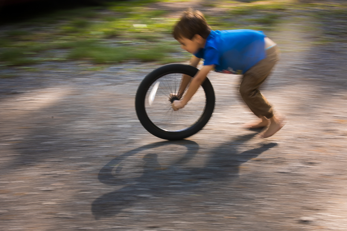 boy in blue shirt running with wheel slow motion blur artistic creative family photographer
