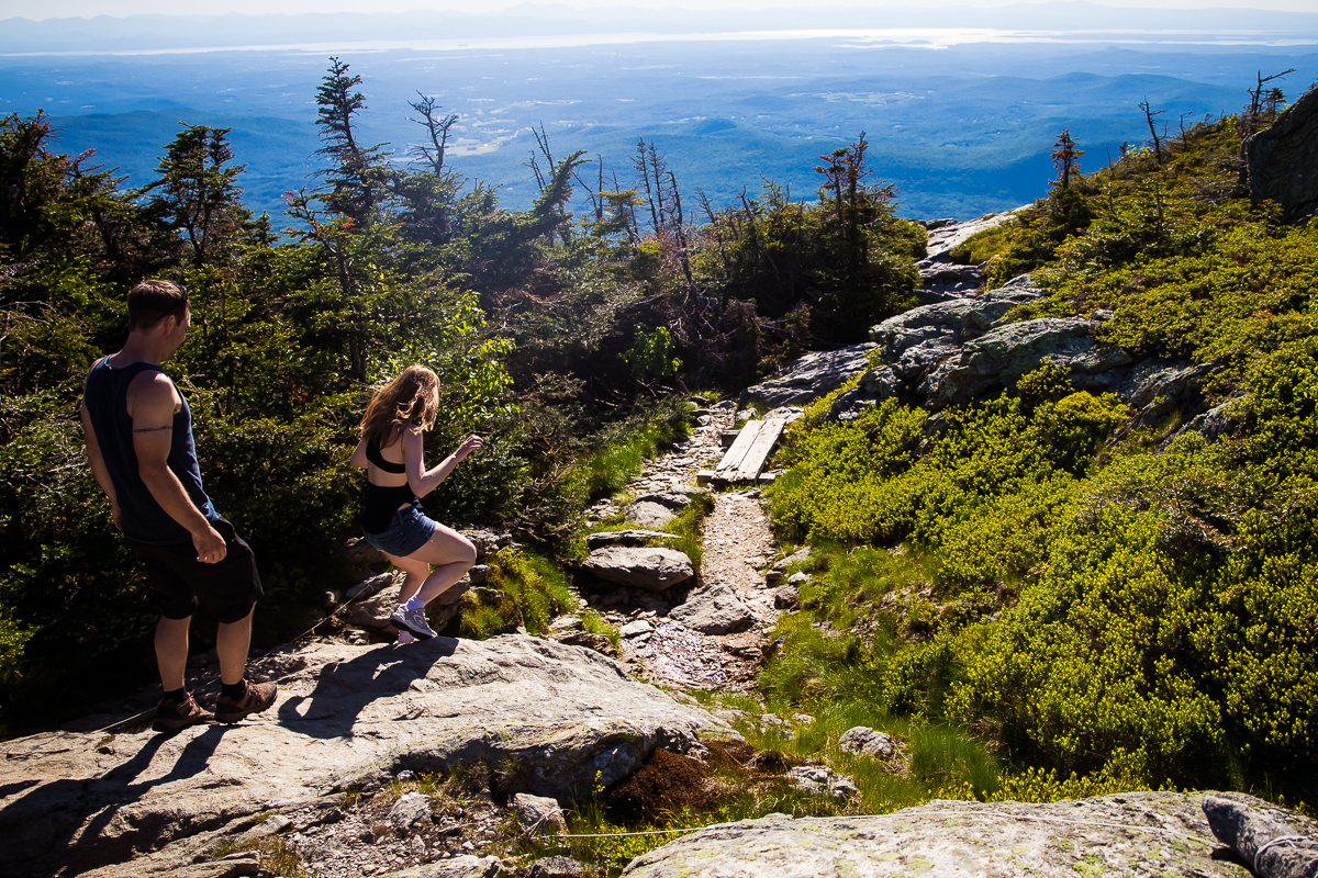 couple walking down mountain in burlington vt along path surrounded by greenery trees and mountains in the distance