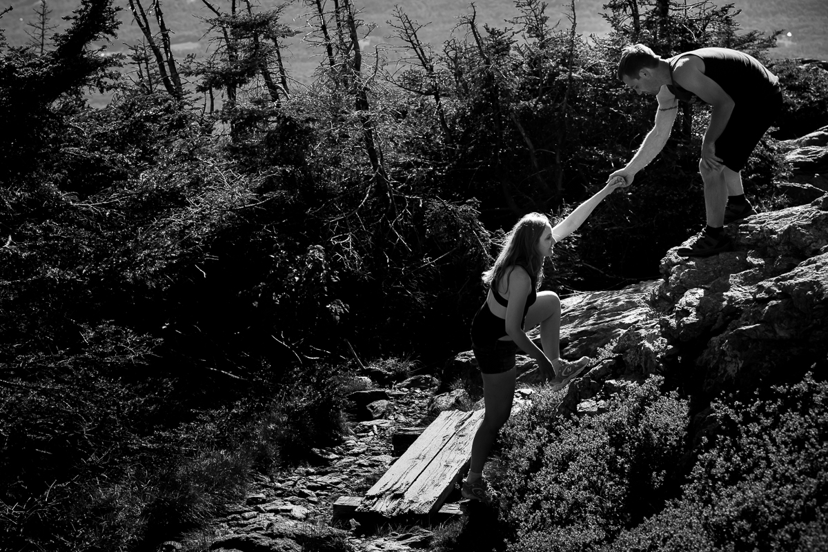 black and white photo of guy helping girl up a steep part of the mountain by holding her hand with trees in distance best natural candid outdoor lifestyle photographer