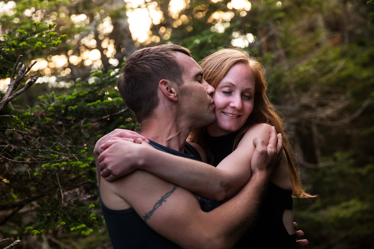 guy kissing girl on cheek while they hold on to each other outside as golden hour shows through the trees with pine trees behind them