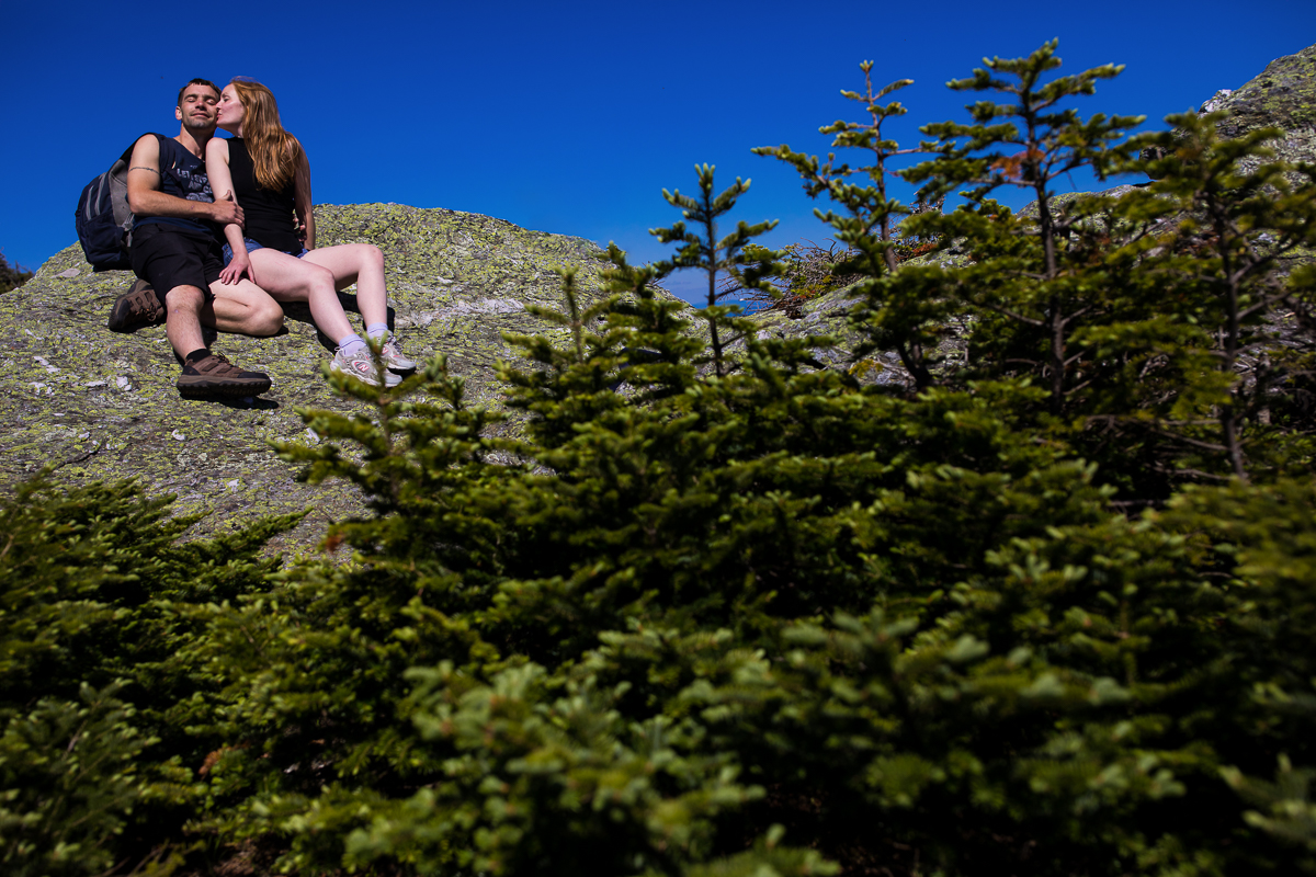 girl kissing guy on cheek while sitting on top of mountain with pine trees in front of them and vibrant blue cloudless sky behind them