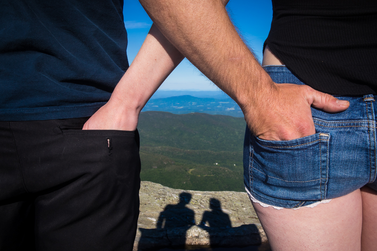 couple with hands in each others back pockets with shadow in front of them standing on top of mountain with sky and mountains in the distance creative unique perspective