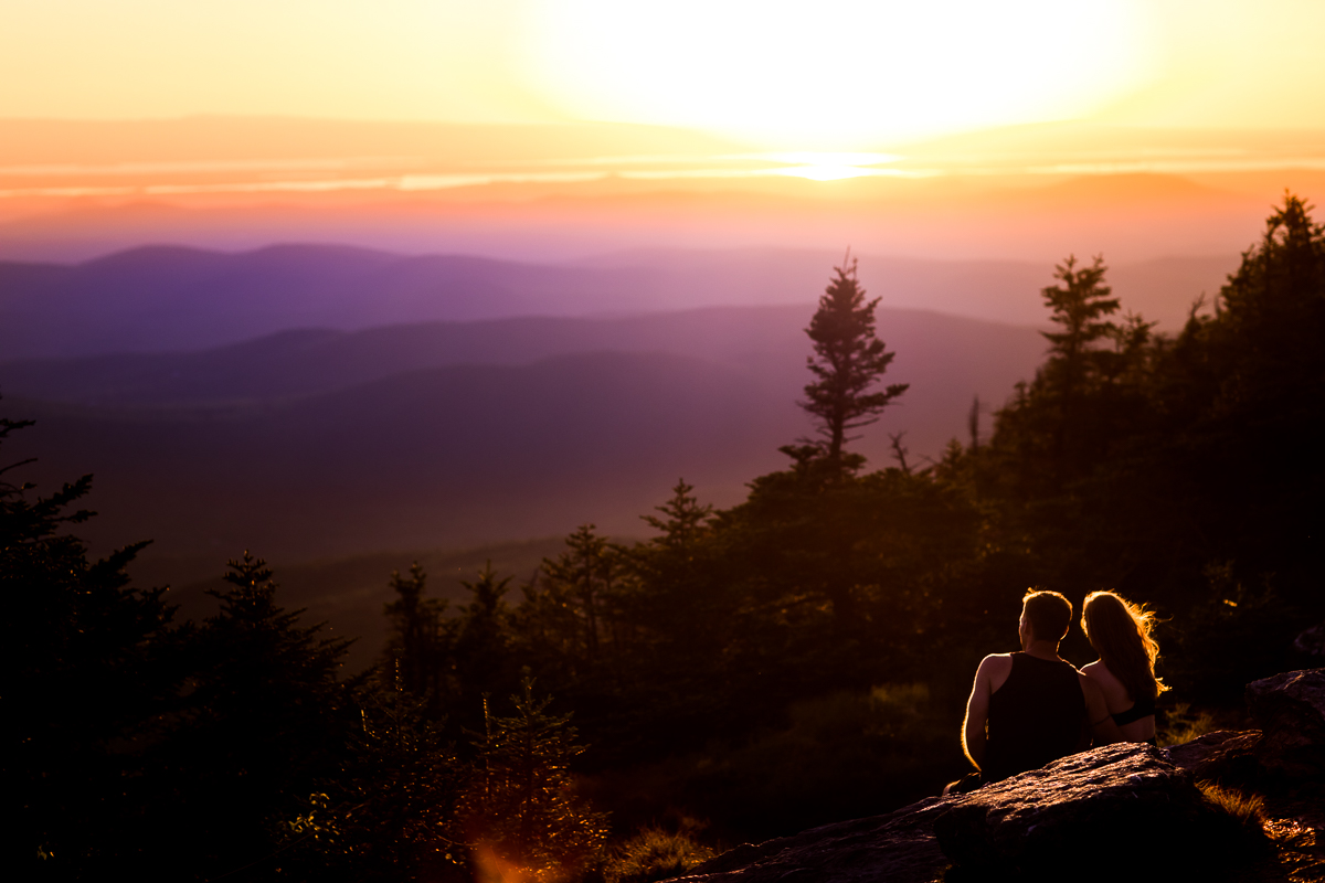 couple sitting on rock on top of mount Mansfield in vermont with trees surrounding and sunset in background best central pa outdoor photographer