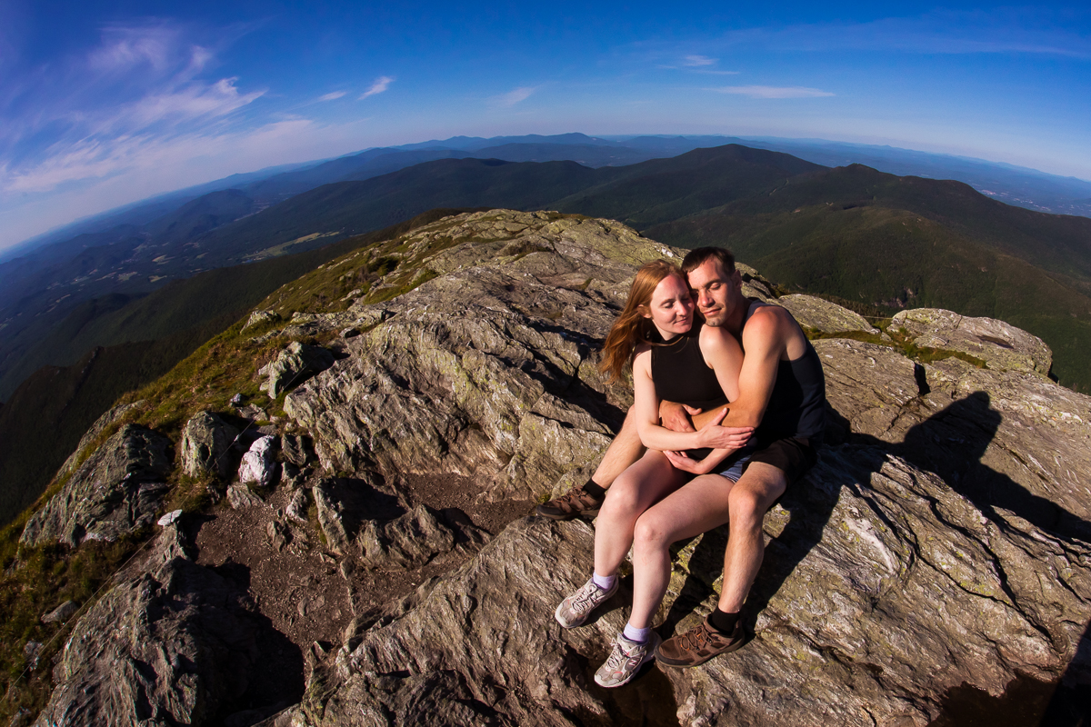 couple sitting down hugging each other on top of summit of mount Mansfield in Burlington with more mountains in the distance fish eye lens wide angle creative vibrant photo
