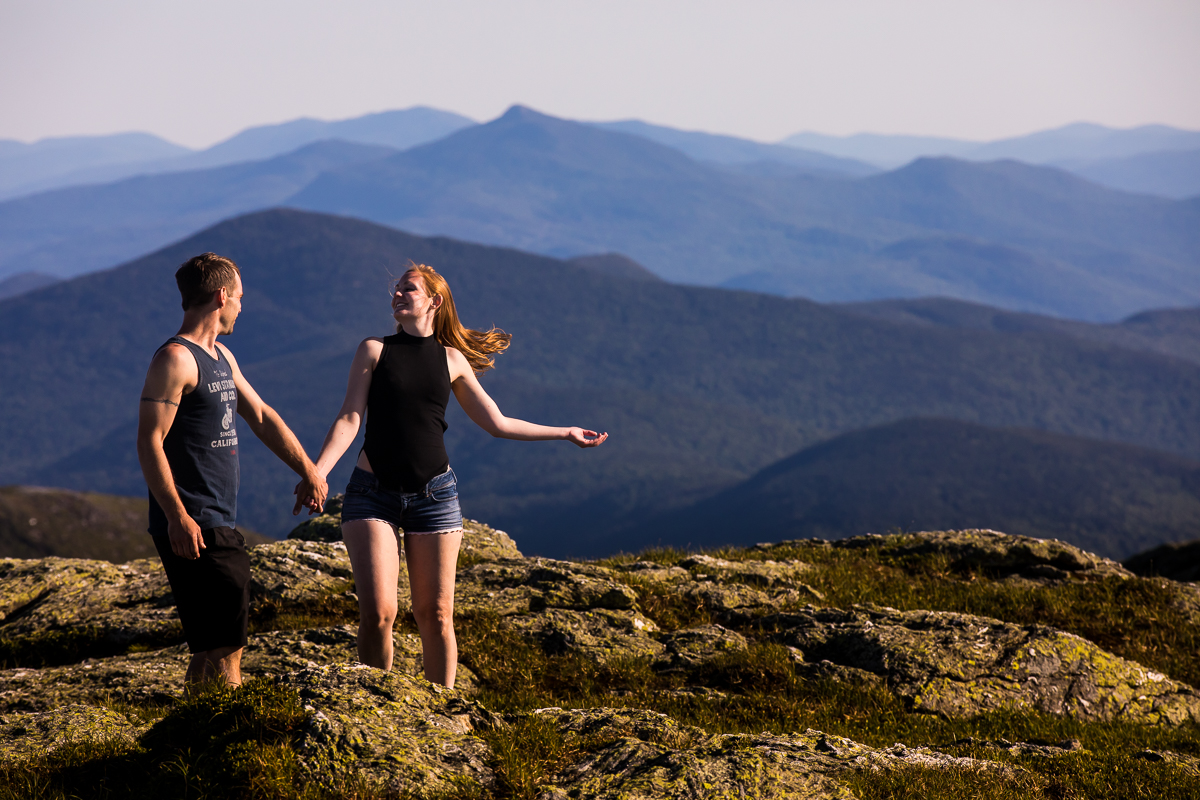 couple walking on top of mountain with more mountains in the background natural candid photographer central pa