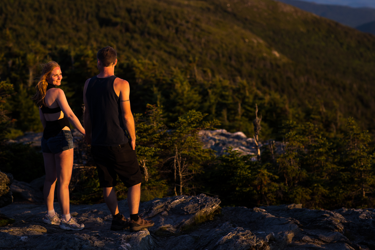 couple standing on top of mountains holding hands smiling at each other while golden hour light shines on them pine trees in the distance