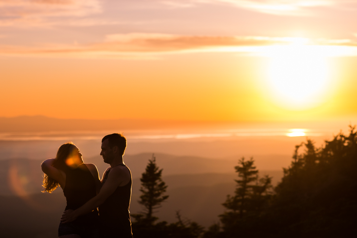 couple looking at each other with orange vibrant sunset in the background and solar flare