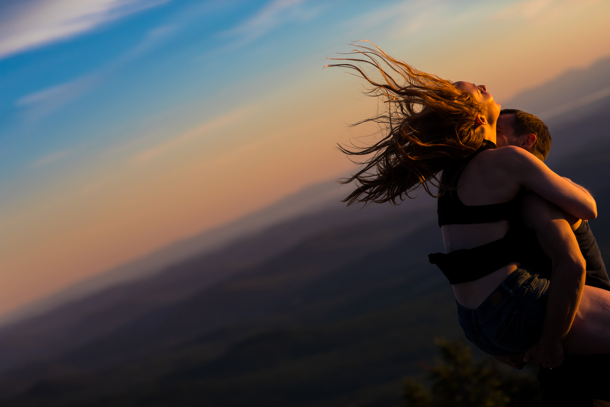 guy picking up girl on top of mountain while girls hair blows in the wind with orange sunset in the background