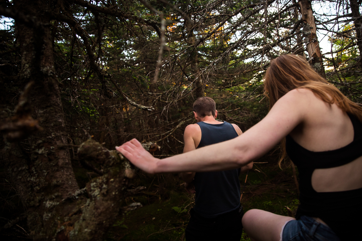 couple hiking through the woods in vermont surrounded by trees wearing athletic clothes