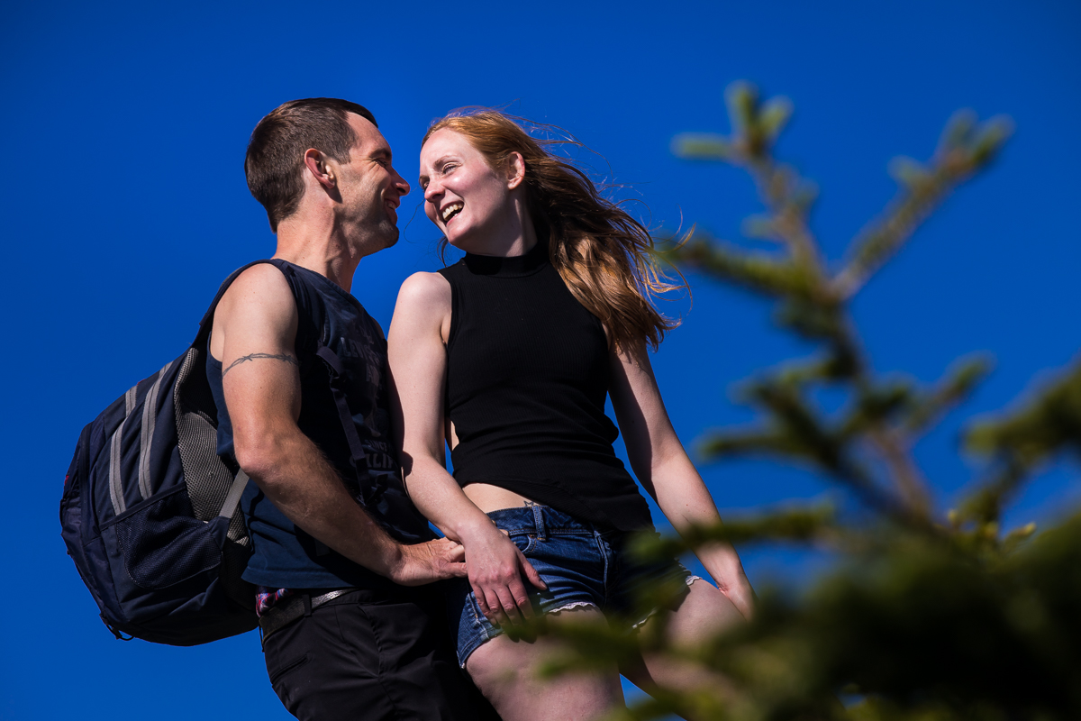 couple laughing and smiling while looking at each other on top of mountain with blue sky in the background and pine tree in foreground best outdoor lifestyle photographer natural candid vibrant
