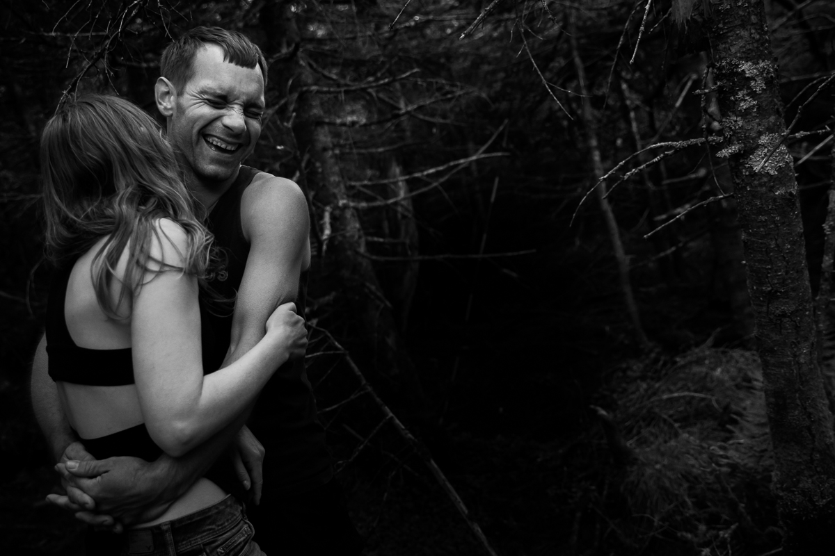 black and white photo of couple hugging while laughing outside in middle of woods surrounded by trees best emotional candid natural outdoor lifestyle photographer